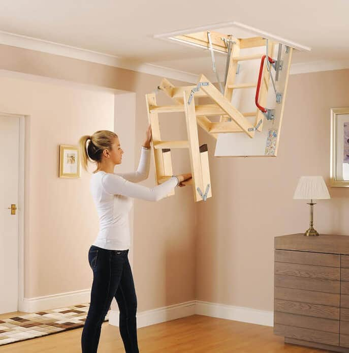 Lady pulling down attic ladder from ceiling