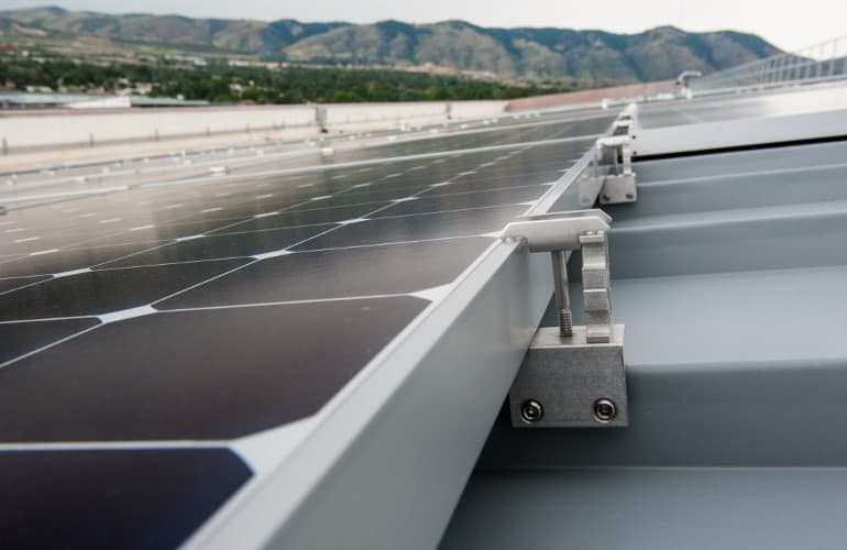 Solar panels with brackets fixed to metal roof